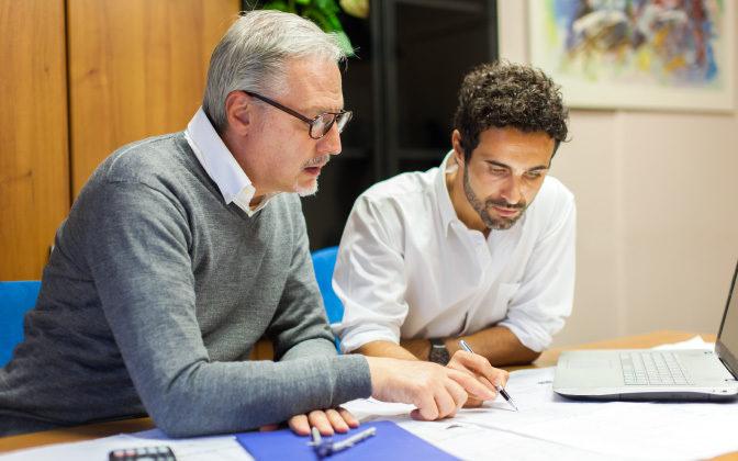 Two Men Working Together At Desk