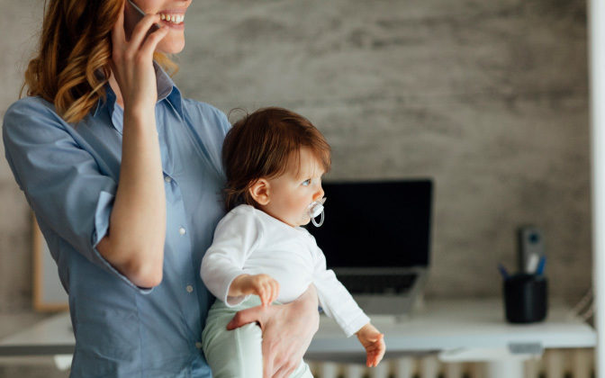 Woman Talking On Phone And Holding Baby