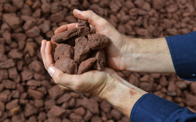 Two Hands Holding Iron Ore Sample